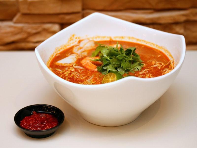Фирменный сингапурский вид перанаканского блюда лакса - это лакса катонг