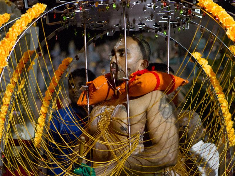 Участники шествия во время фестиваля Тайпусам несут на себе оригинально украшенные конструкции